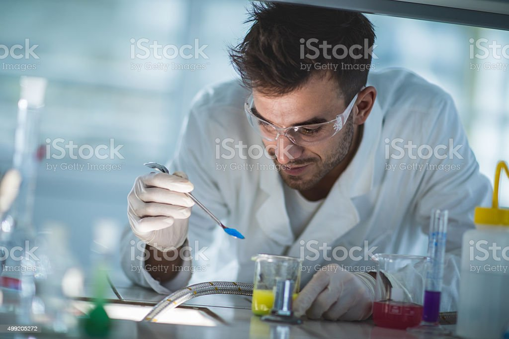 Smiling scientist examining chemical substances in a laboratory. stock photo