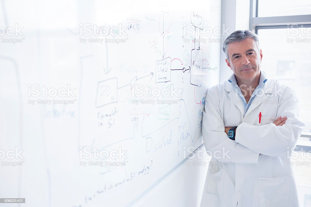 Smiling scientist leaning against the whiteboard stock photo