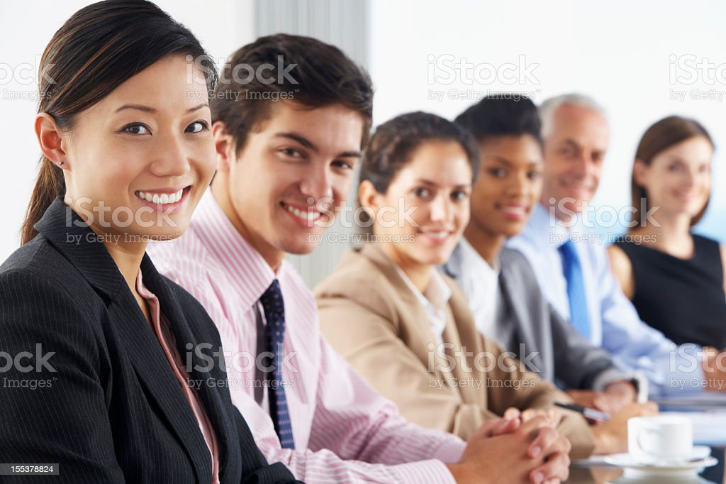 Smiling seated business people listening to presentation royalty-free stock photo