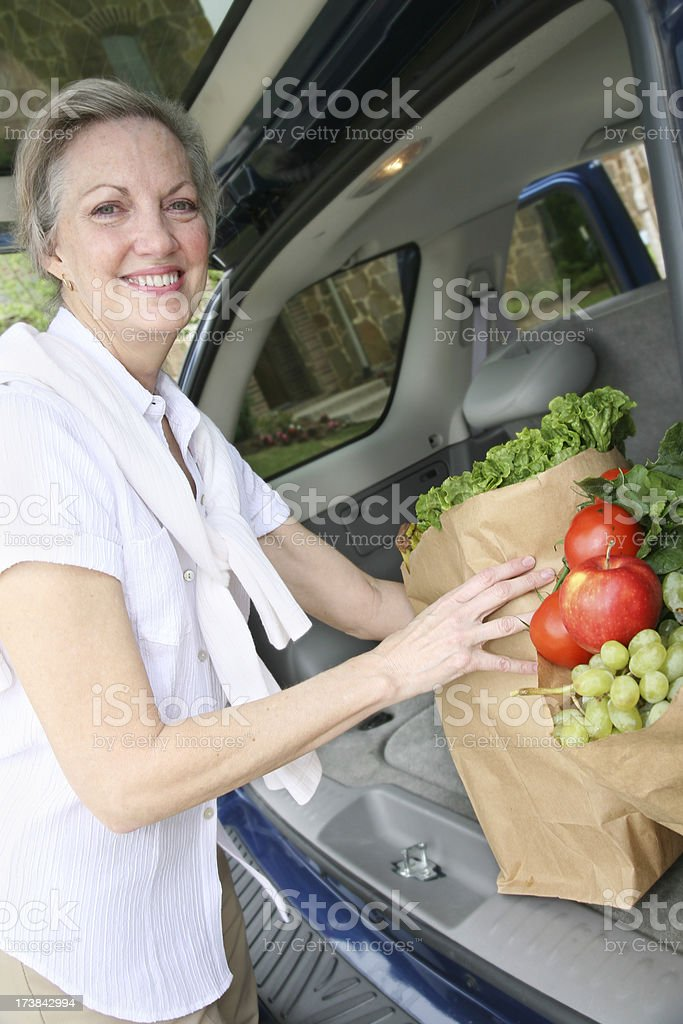Smiling Senior Adult Taking Groceries from Car royalty-free stock photo
