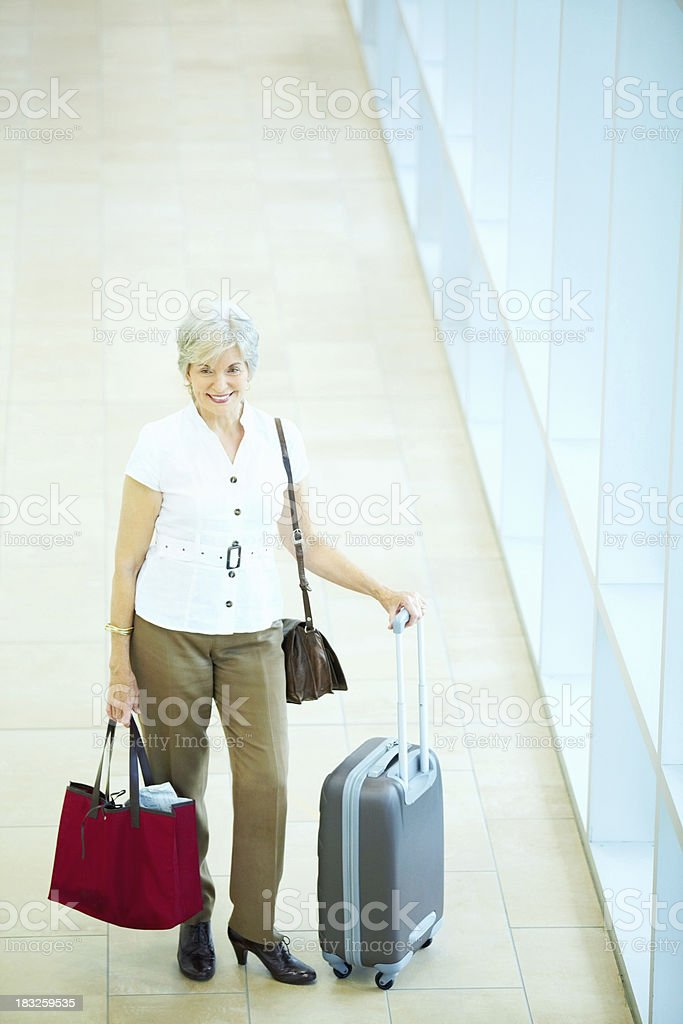 Smiling senior business woman with baggage's in an airport royalty-free stock photo