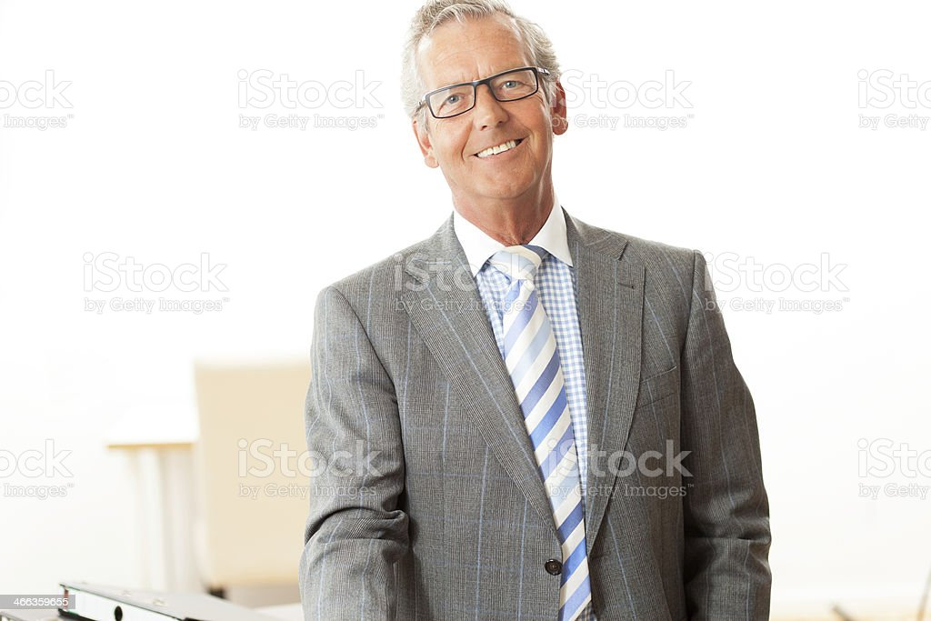 Smiling senior businessman in a gray suit and striped tie stock photo