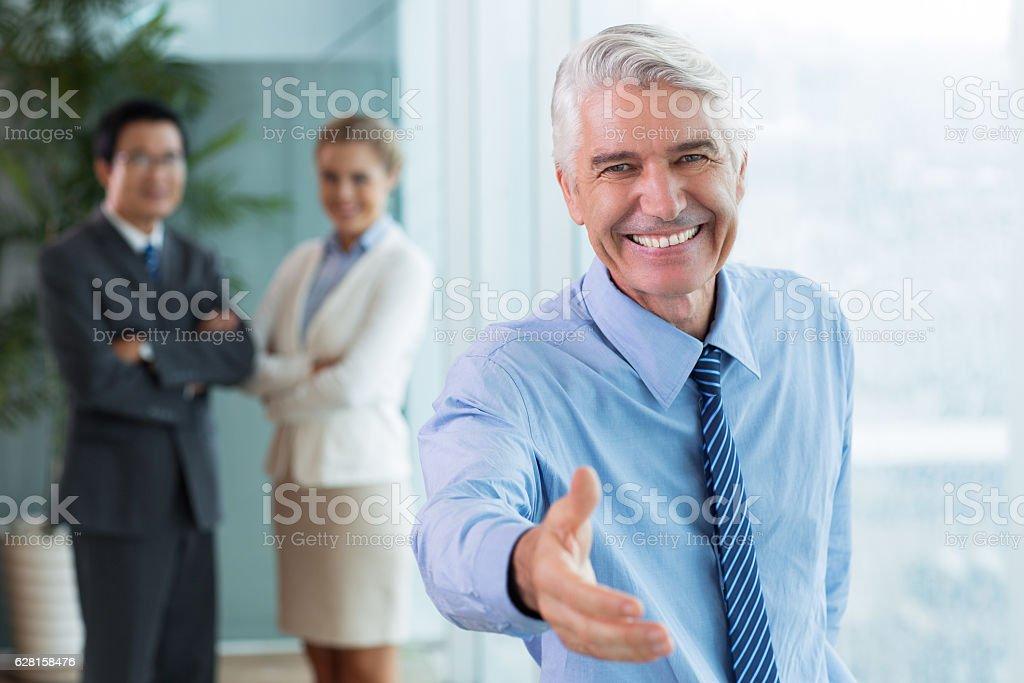 Smiling senior businessman offering to shake hands stock photo