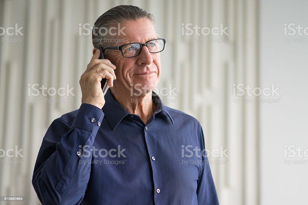 Smiling Senior Businessman Talking on Smartphone stock photo