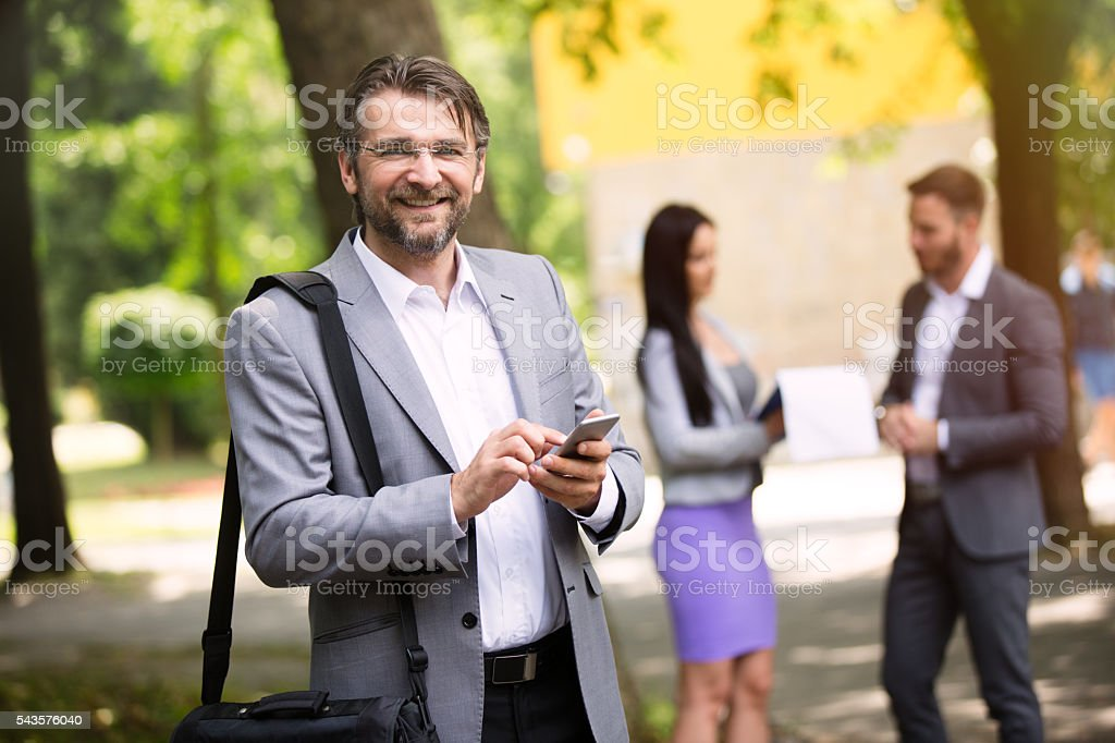 Smiling senior businessman text messaging in the park. stock photo