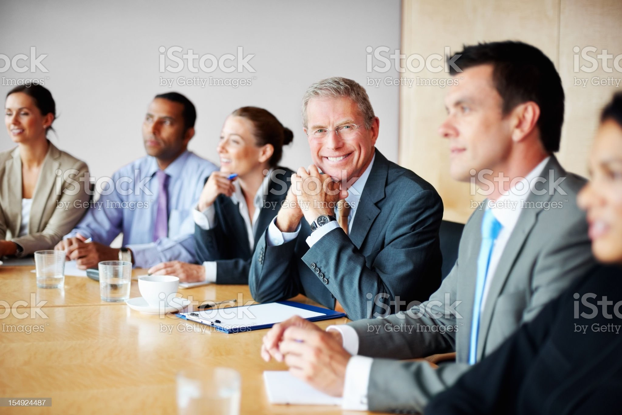 Smiling senior businessman with his team in a meeting royalty-free stock photo