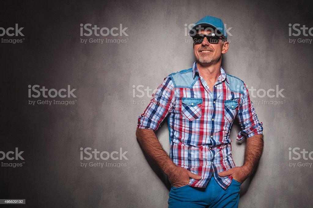smiling senior casual man wearing baseball hat looking away stock photo