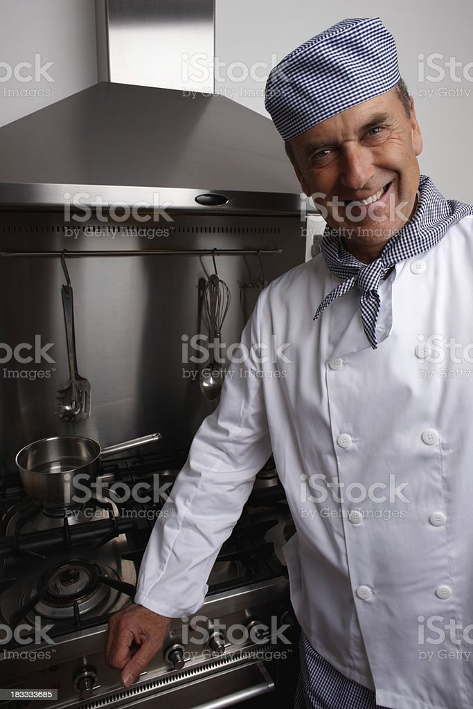 Smiling senior chef standing by gas stove and vent hood royalty-free stock photo