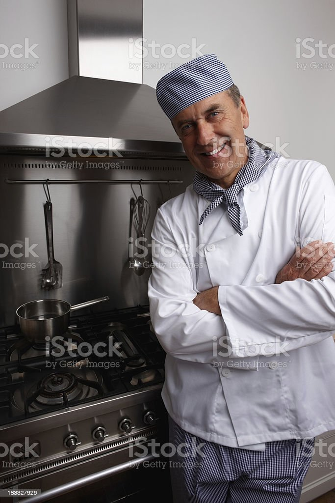 Smiling senior chef with hands folded standing by gas stove royalty-free stock photo