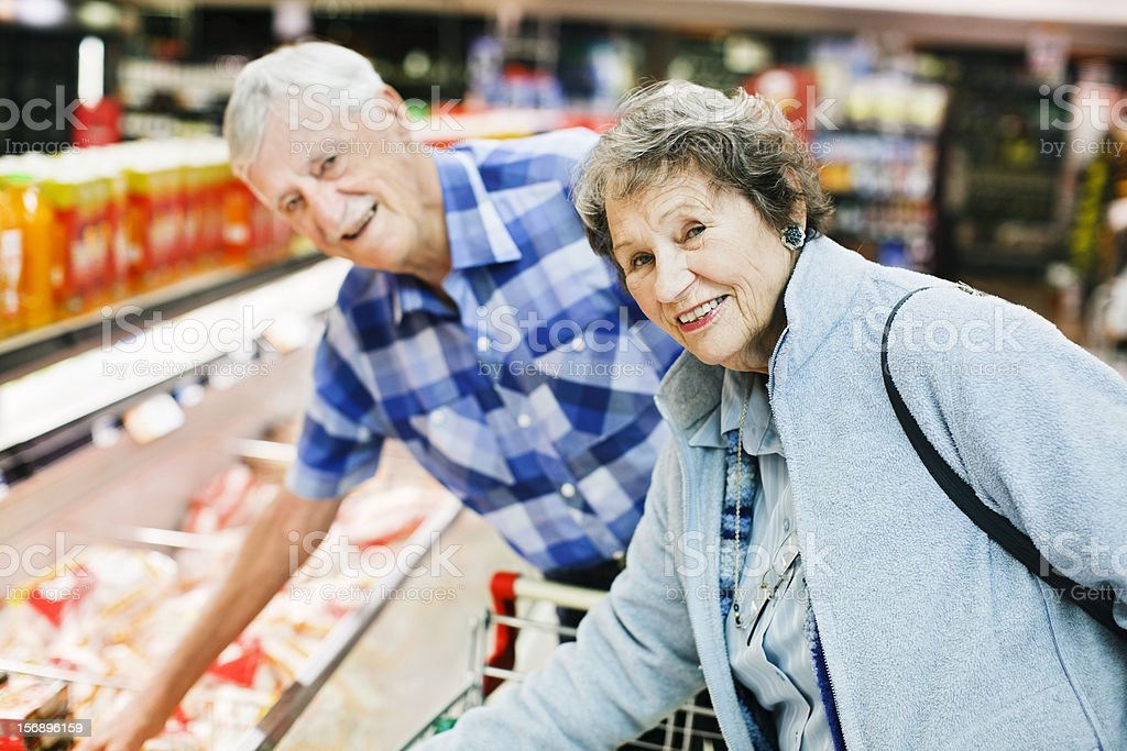 Smiling senior couple bend over fridge in supermarket, choosing chicken stock photo