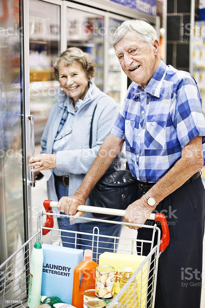 Smiling senior couple check fridge contents while shopping in supermarket stock photo