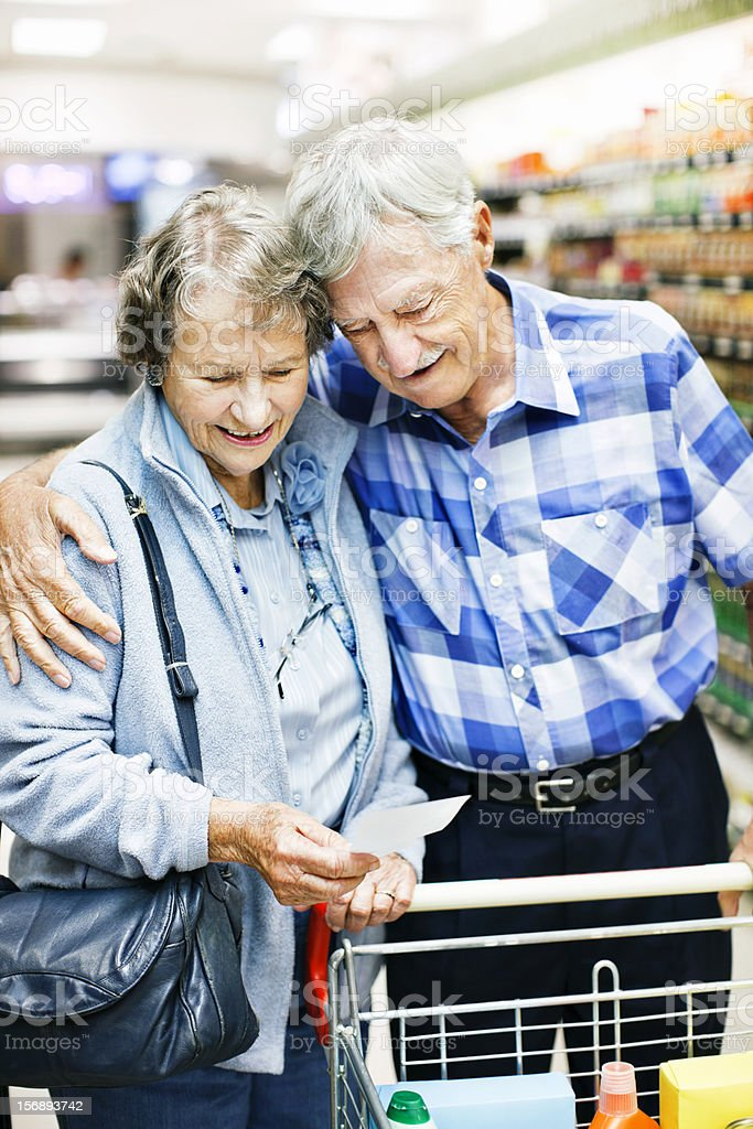 Smiling senior couple check shopping list in supermarket stock photo
