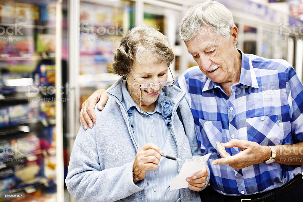 Smiling senior couple check their shopping list in supermarket stock photo