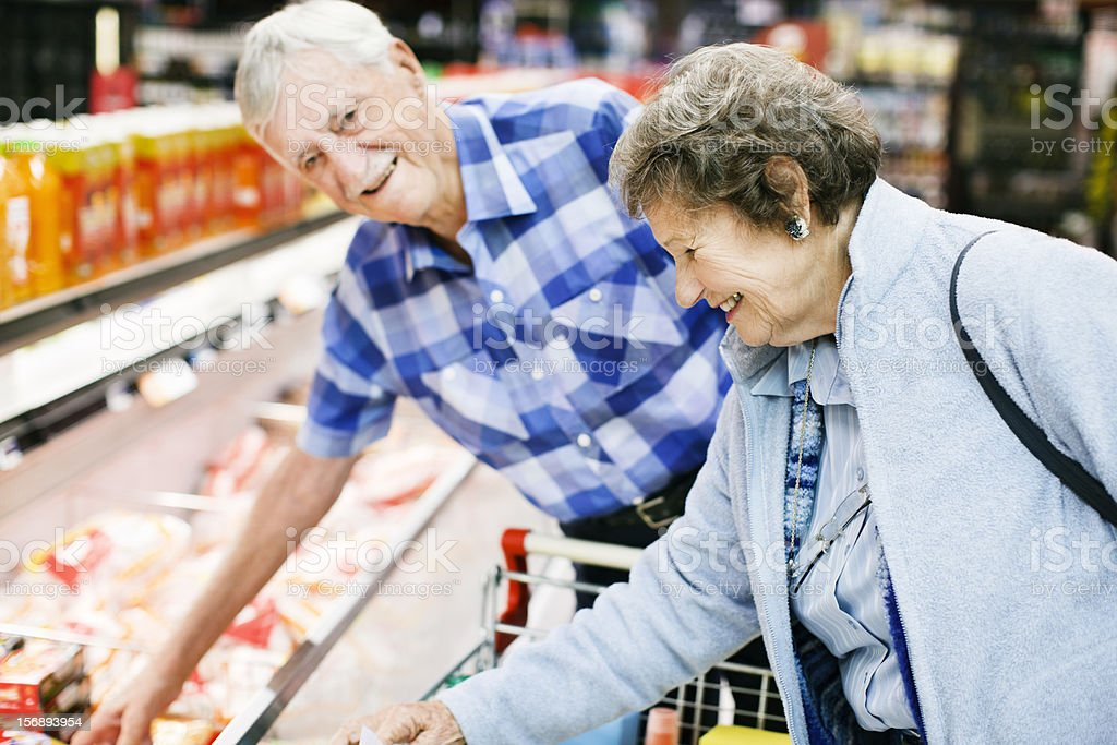 Smiling senior couple choosing chicken in a supermarket fridge stock photo