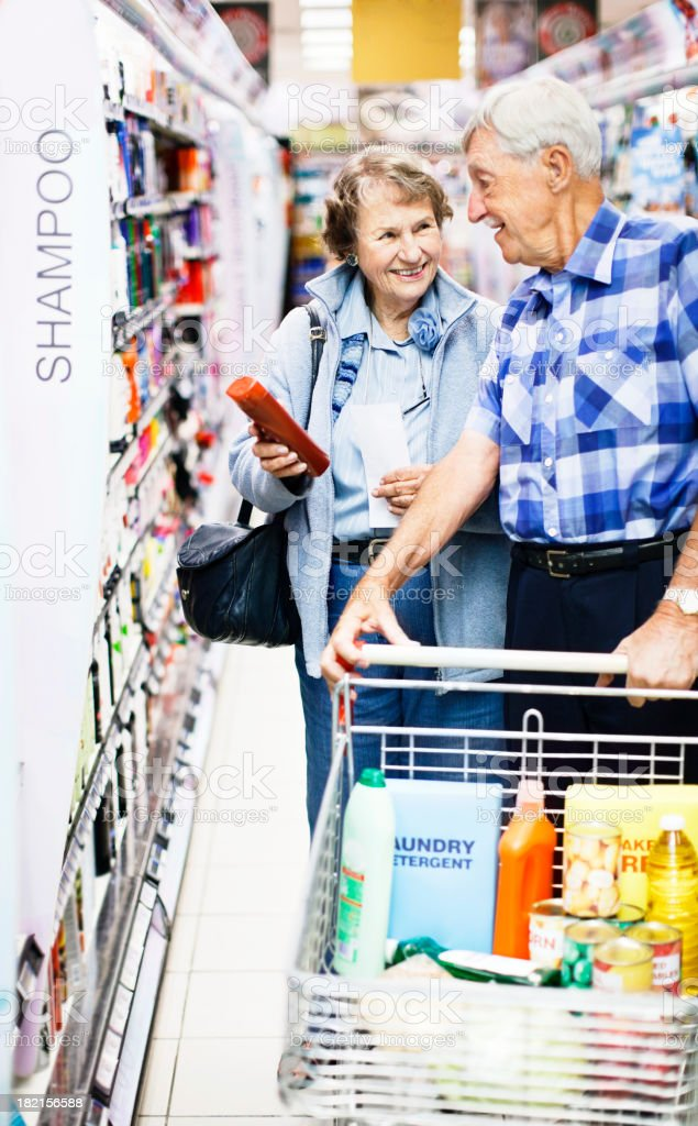 Smiling senior couple choosing toiletries in supermarket stock photo