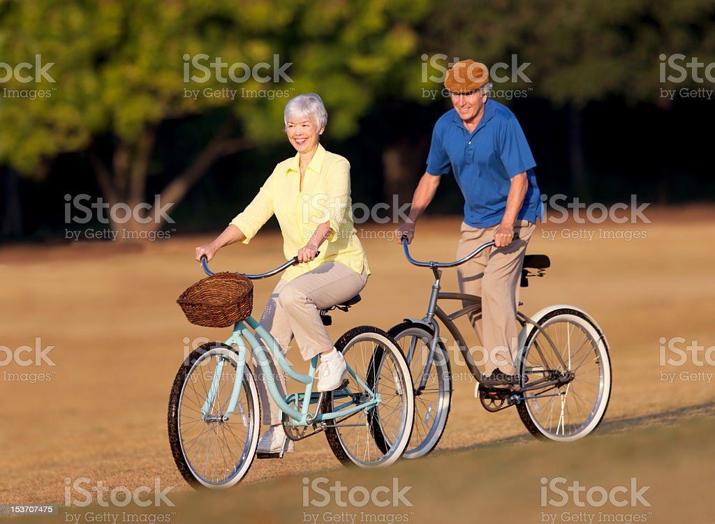 Smiling senior couple cycle along a path in the sun royalty-free stock photo