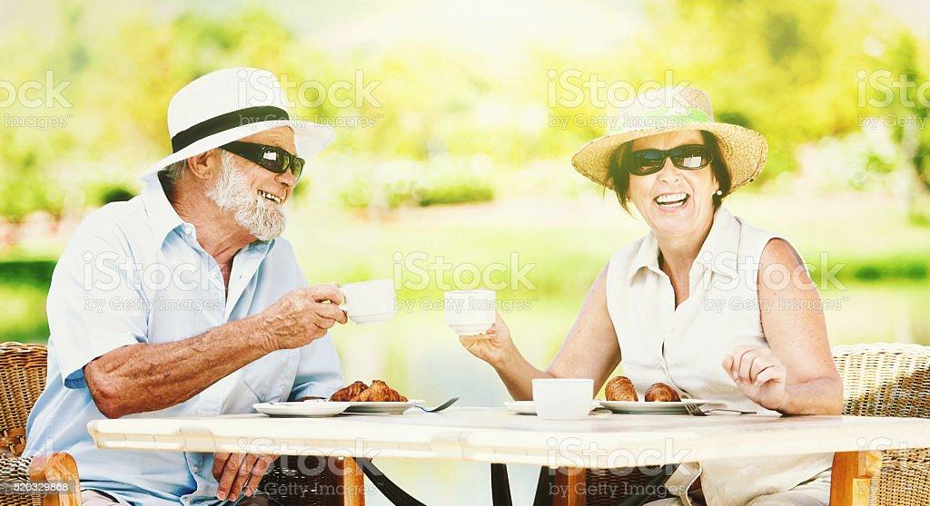 Smiling senior couple enjoying coffee in the sunshine stock photo