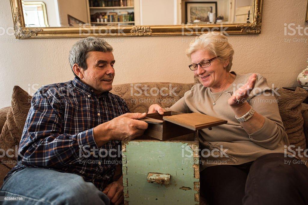 Smiling senior couple evoking their memories at home. stock photo