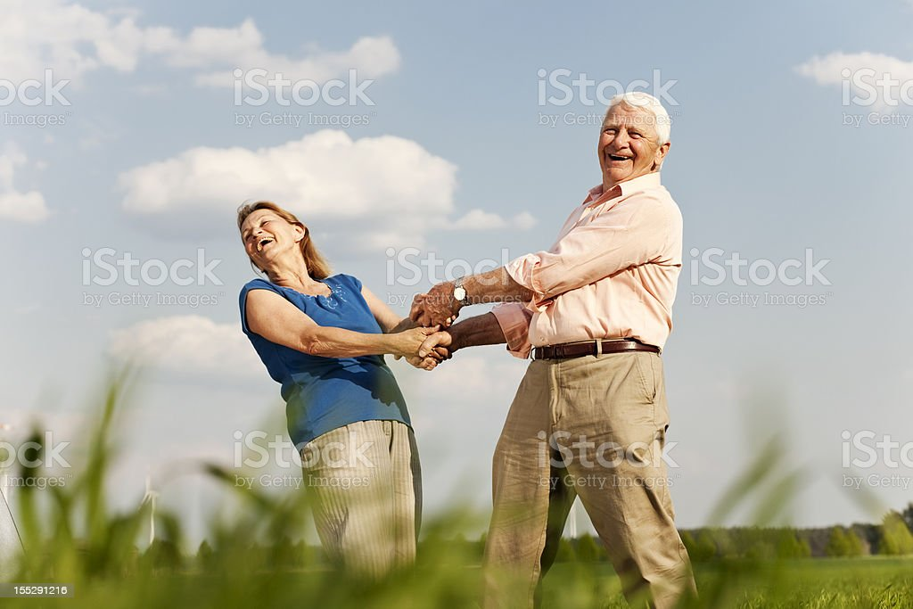 Smiling senior couple, holding hands and spinning around  royalty-free stock photo