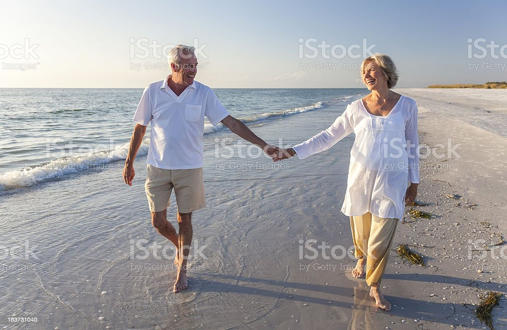 Smiling senior couple holding hands on a beach stock photo