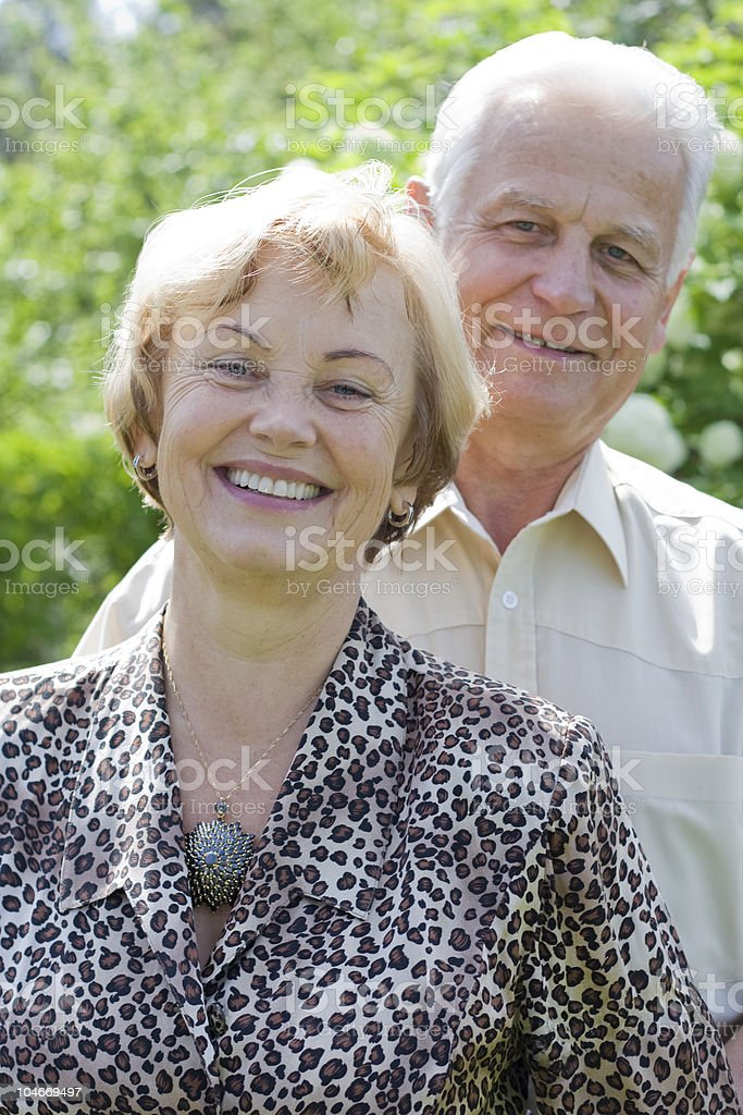 Smiling senior couple in the blossoming garden royalty-free stock photo