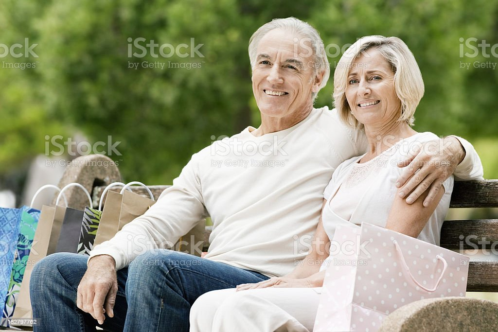 Smiling Senior Couple On Park Bench With Shopping Bags royalty-free stock photo
