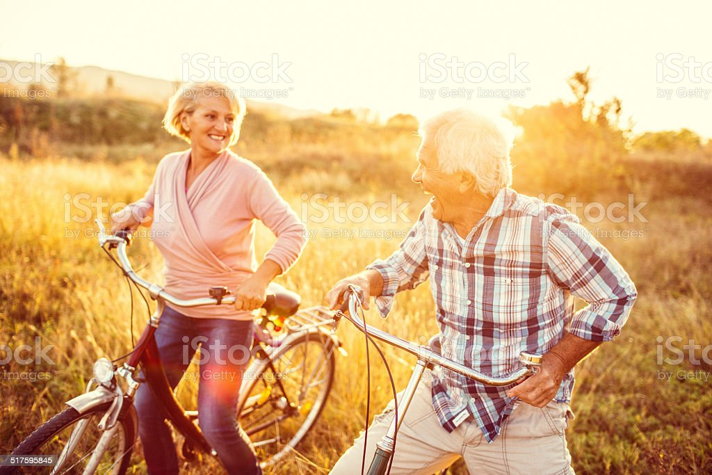 Smiling senior couple riding bicycles stock photo