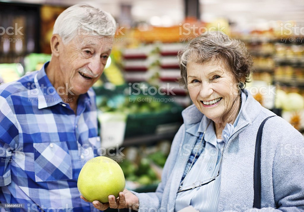 Smiling senior couple selecting grapefruit in supermarket stock photo