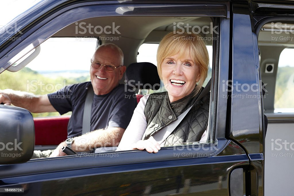 Smiling senior couple sitting in campervan royalty-free stock photo