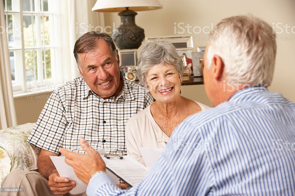 Smiling senior couple sitting on couch with advisor royalty-free stock photo