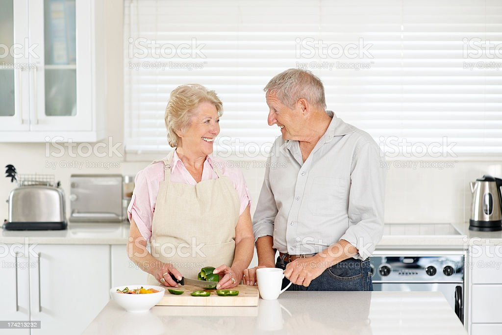 Smiling senior couple standing together in the kitchen stock photo