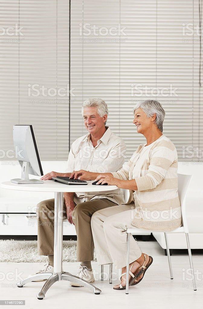 Smiling senior couple using computer royalty-free stock photo