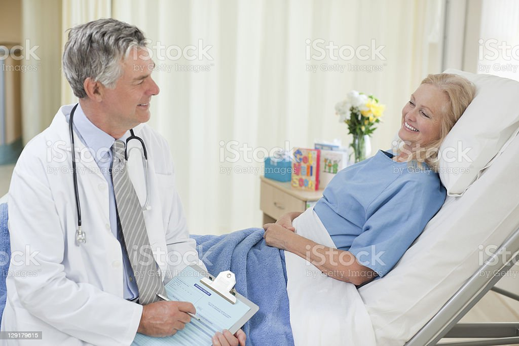 Smiling senior doctor talking with patient royalty-free stock photo
