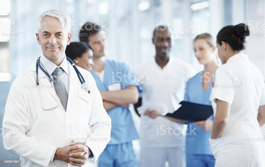 Smiling senior doctor with medical team discussing in background royalty-free stock photo