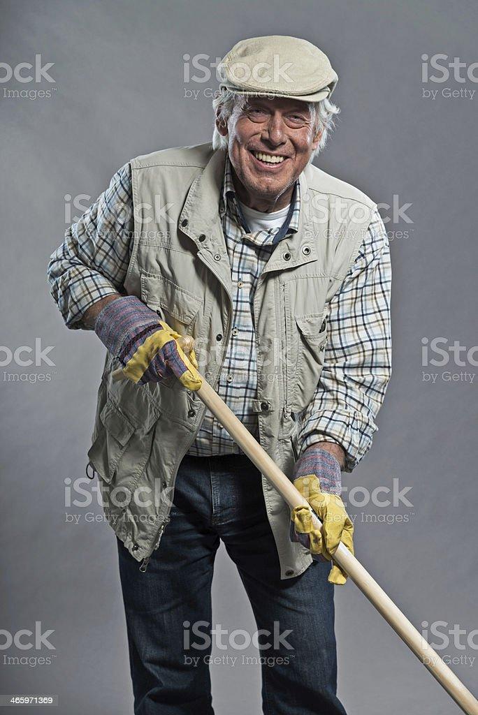 Smiling senior gardener man with hat holding hoe. Studio shot. royalty-free stock photo
