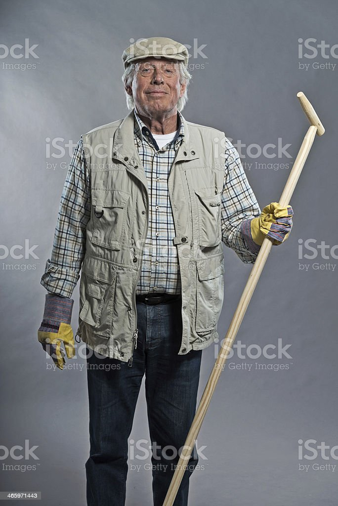Smiling senior gardener man with hat holding hoe. Studio shot. royalty-free stock photo
