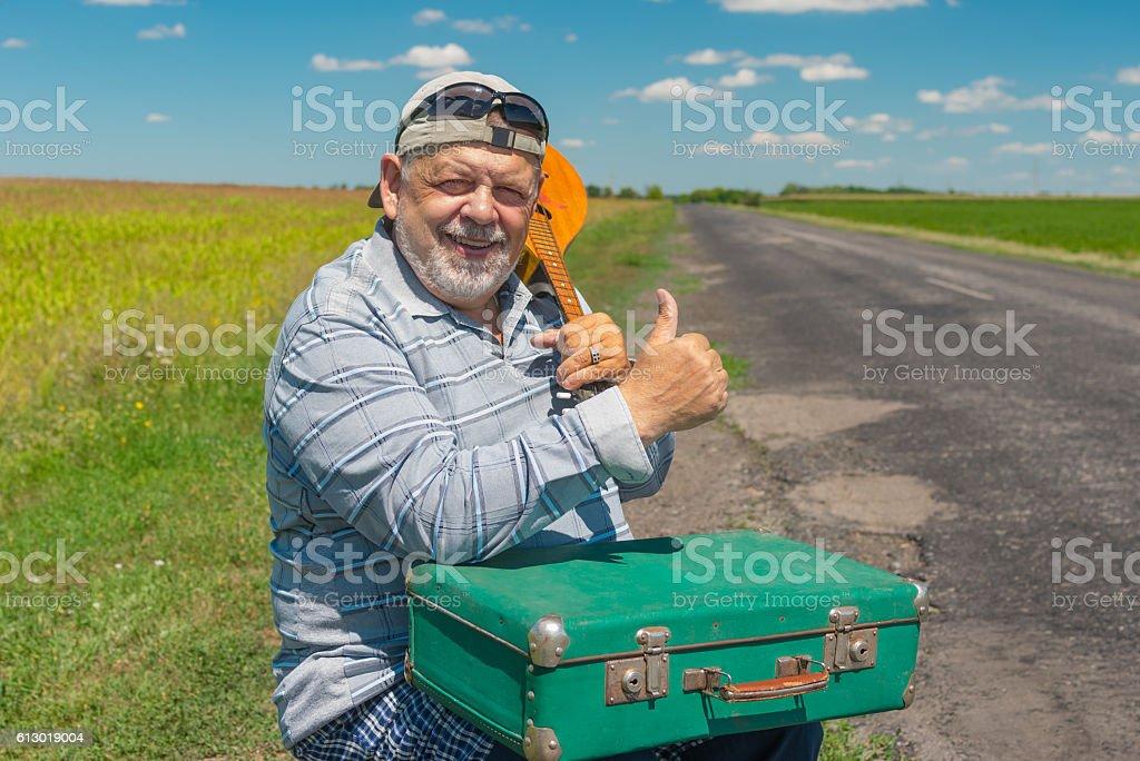 Smiling senior hiker having short rest on a roadside stock photo