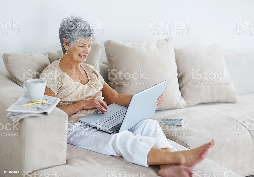 Smiling senior lady using a laptop while sitting on couch royalty-free stock photo