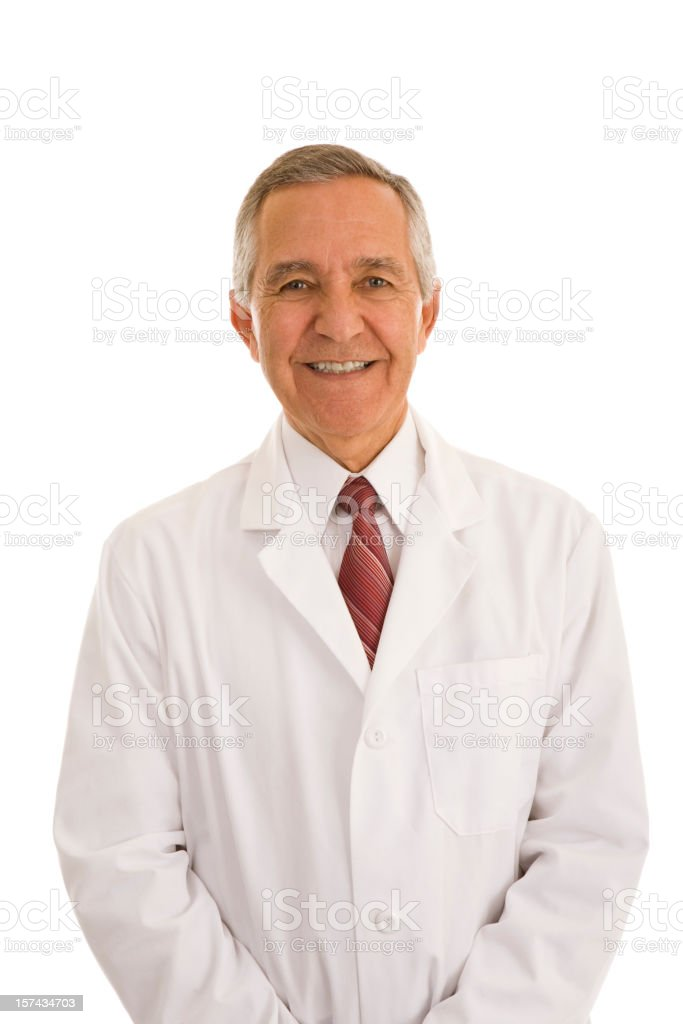 Smiling senior male wearing lab coat hands in pocket stock photo