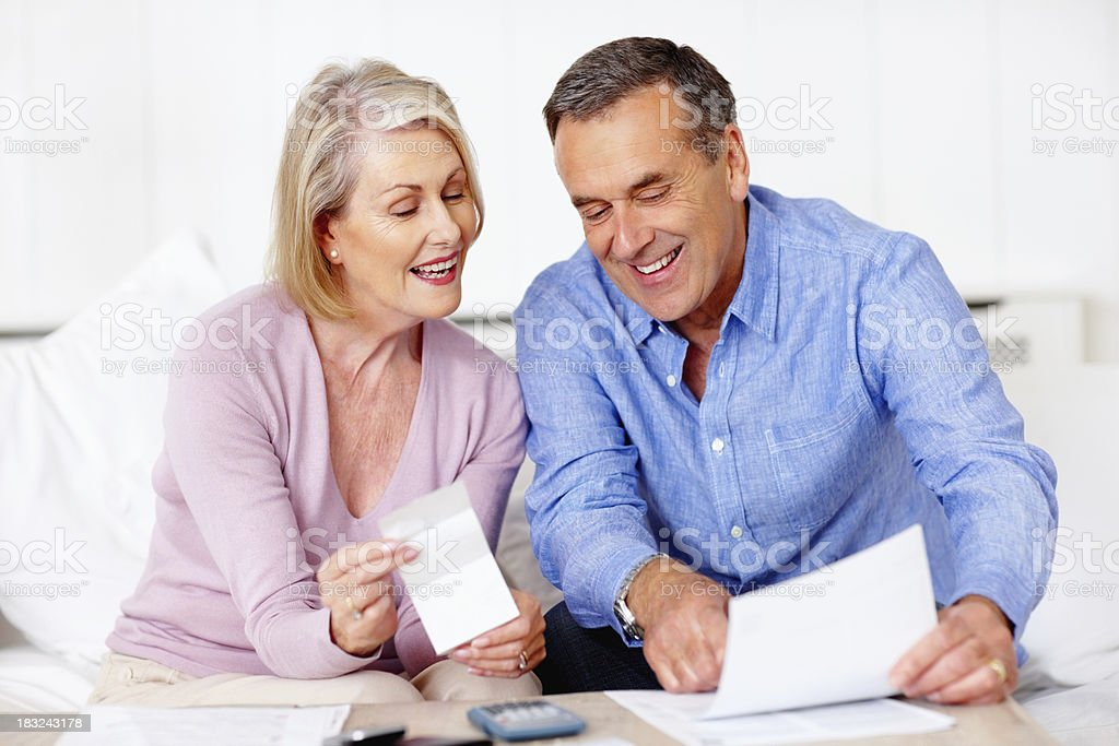 Smiling senior man and wife looking at their daily expenses royalty-free stock photo