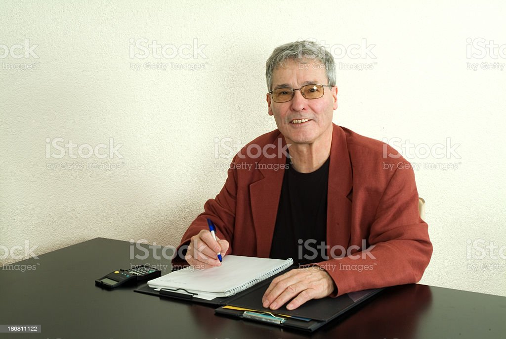 Smiling senior man behind desk with office supply royalty-free stock photo
