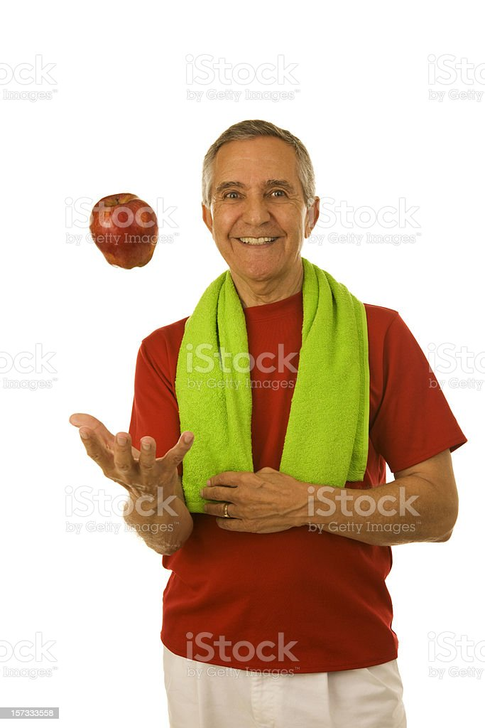 Smiling senior man in workout attire tossing red apple royalty-free stock photo