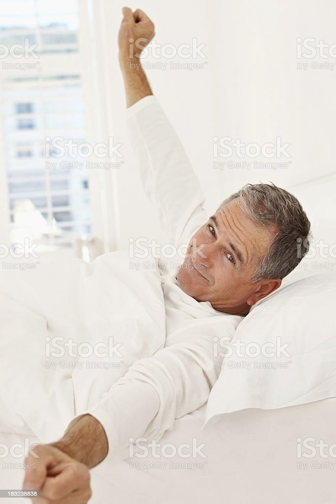 Smiling senior man just woken up in bed royalty-free stock photo