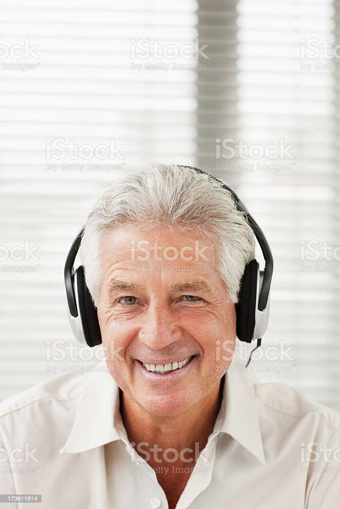 Smiling senior man listening to headphones royalty-free stock photo