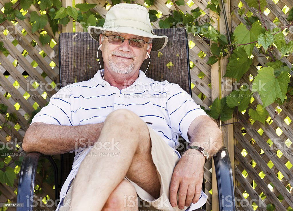 Smiling senior man listening to music stock photo