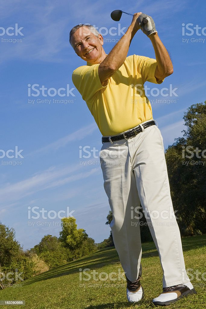 Smiling senior man on golf course swinging club royalty-free stock photo