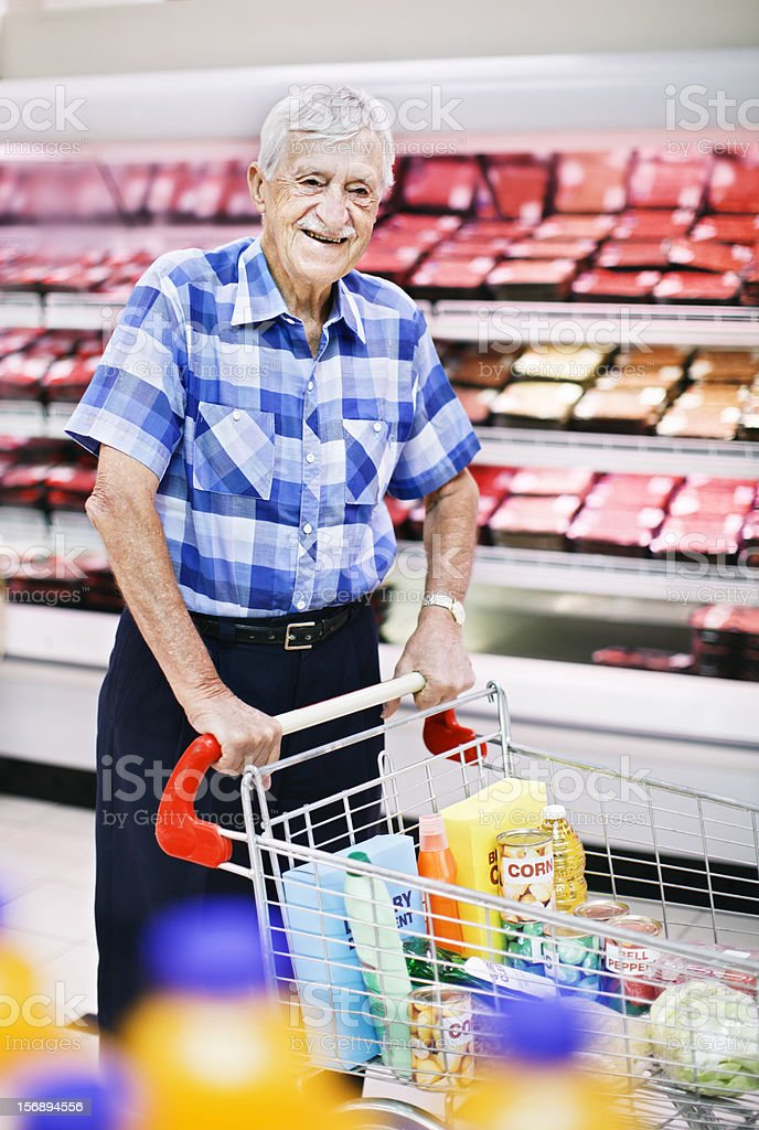 Smiling senior man pushes trolley past supermarket meat fridges stock photo