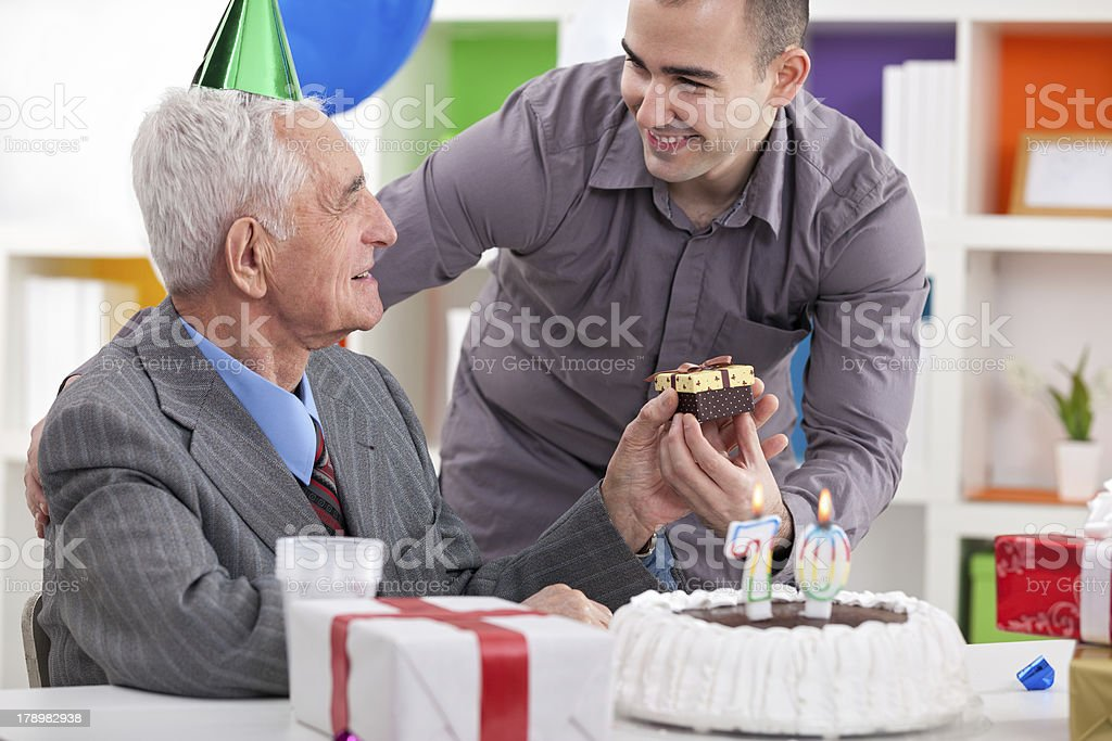 Smiling senior man receiving gift for birthday royalty-free stock photo