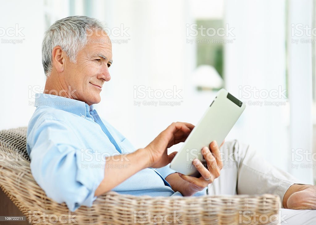 Smiling senior man sitting on couch holding a tablet PC royalty-free stock photo