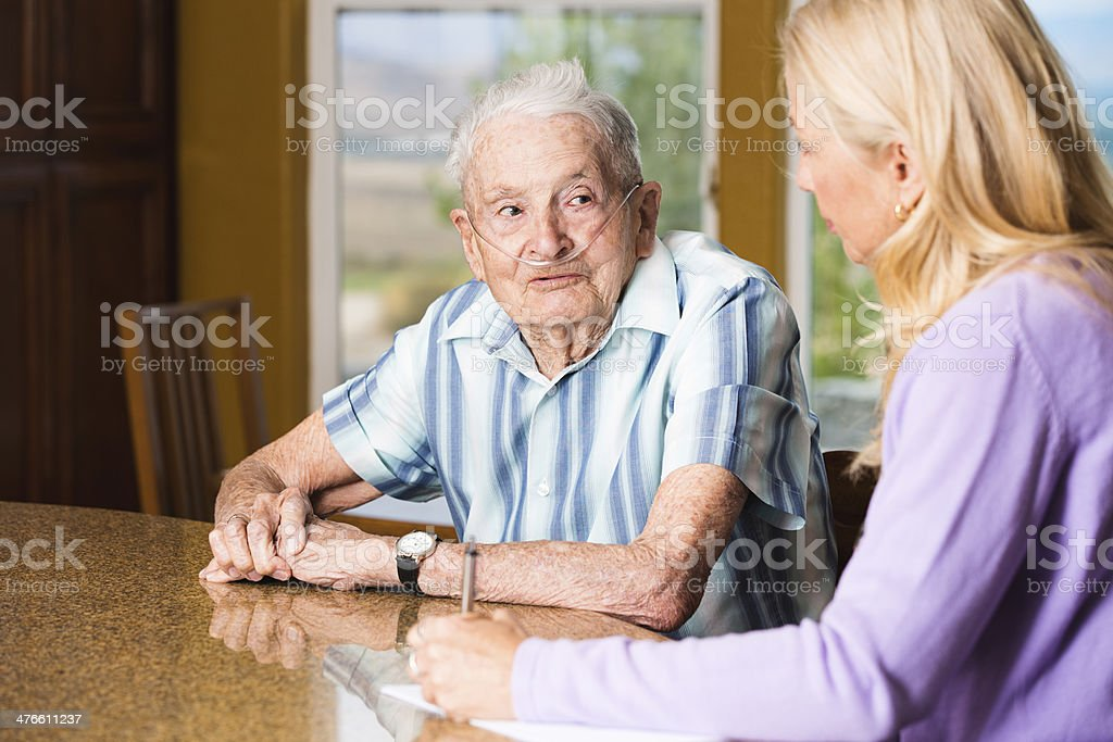 Smiling senior man talking to social worker at the counter stock photo